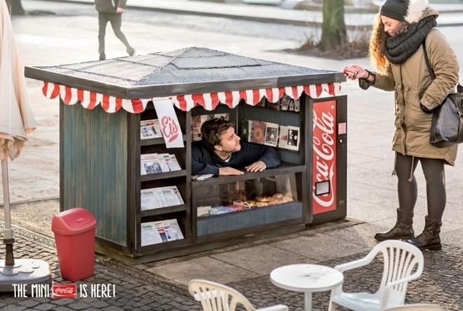 """Để giới thiệu Coca-Cola dạng lon mini tại Đức, hãng đồ uống có ga lớn nhất thế giới đã cho đặt những ki-ốt mini tại 5 thành phố của nước này để bán hàng. Thậm chí tại đây còn có máy bán soda mini. """"Những thứ nhỏ bé trong cuộc sống khiến ta hạnh phúc"""" là khẩu hiệu của chiến dịch này."""